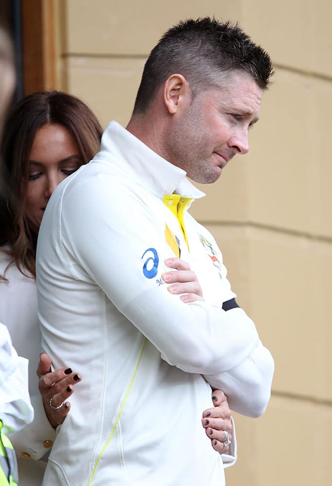 Australia's captain Michael Clarke receives attention to his back from his wife, Kyly, during a rain delay during the second day of their cricket test match against India in Adelaide, Australia.