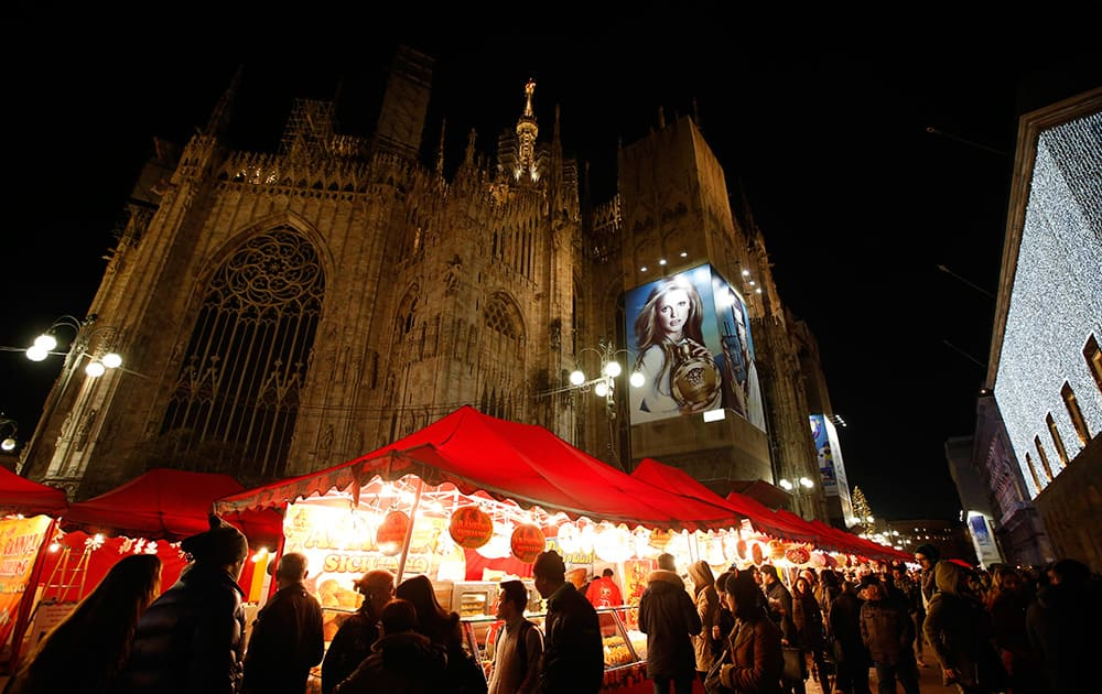 The Duomo gothic cathedral is seen behind a traditional open air Christmas market, in Milan, Italy.