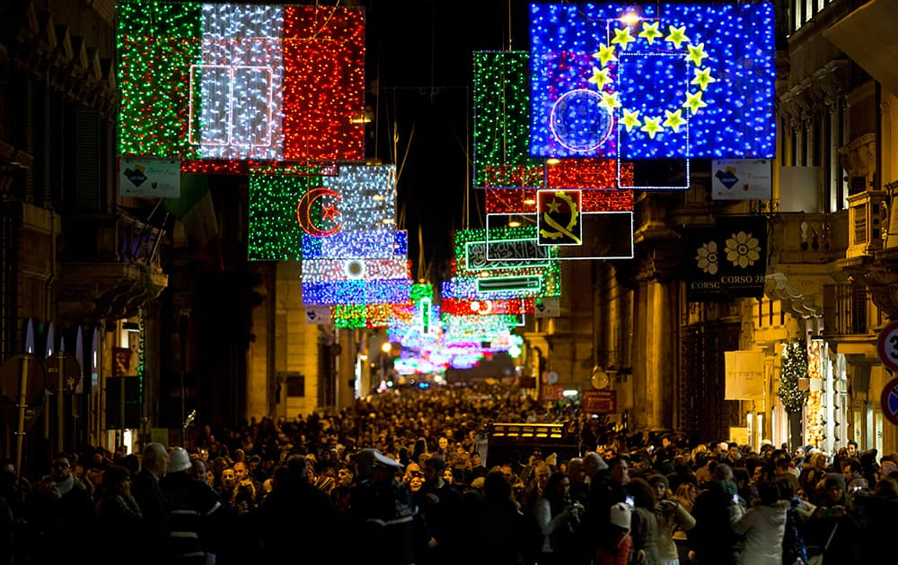 People stroll along Rome's Via del Corso main shopping street, lit up with Christmas decorations representing the world's flags
