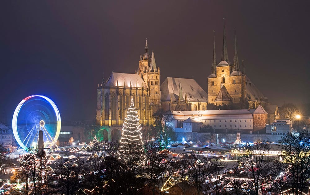More than 200 booths offer traditional Thuringian handicrafts and sweets and a Ferris wheel stand on the Christmas Market in front of the Mariendom (Cathedral of Mary) and St. Severi's Church in Erfurt, central Germany.