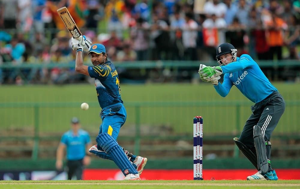 Sri Lankan batsman Kumar Sangakkara plays a shot as England's wicketkeeper Jos Buttler watches during the fifth one day international cricket match between Sri Lanka and England in Pallekele, Sri Lanka.