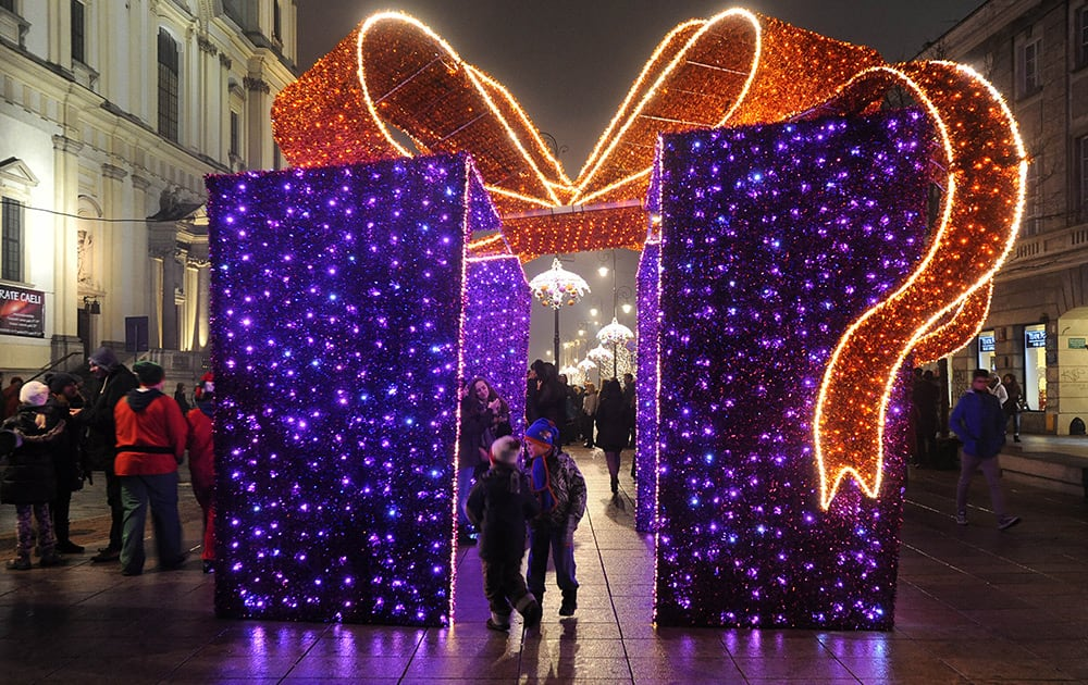 People walk past Christmas decorations on a street in Warsaw, Poland.