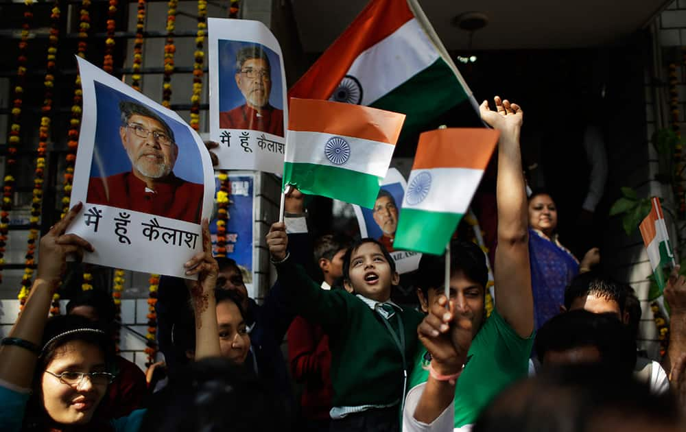 Workers and rescued child laborers at the Bachpan Bachao Andolan, or Save the Children Movement, founded by India's Nobel laureate Kailash Satyarthi wave the Indian flag and display Satyarthi's photographs as they celebrate at the organization's office in New Delhi.