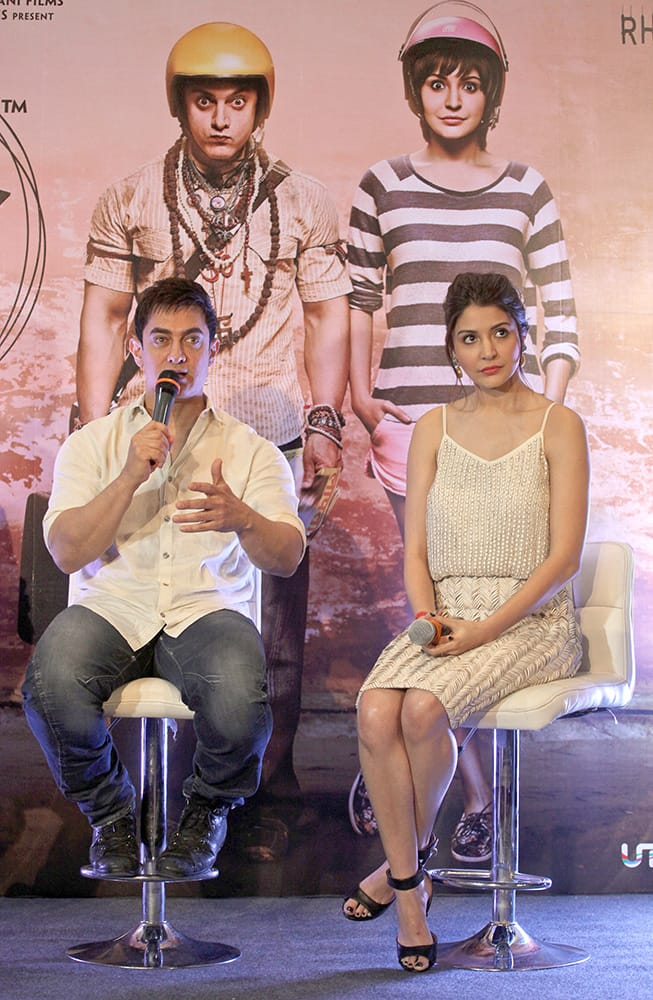 Bollywood actor Aamir Khan speaks seated next to Anushka Sharma during a press conference to promote their film 'PK' in Ahmedabad, India.