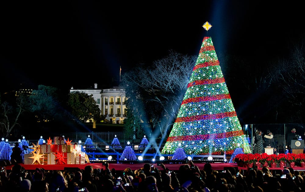 President Barack Obama and the first family stands after lighting the 2014 National Christmas Tree during the National Christmas Tree lighting ceremony at the Ellipse near the White House in Washington.