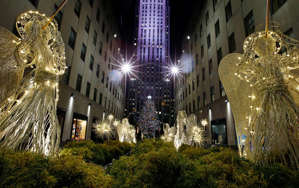 The Rockefeller Center Christmas tree can be seen through the Channel Gardens following a lighting ceremony, in New York.