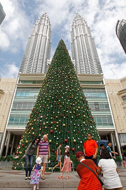 People stand in front of a giant Christmas tree on display against the Malaysia's landmark Petronas Twin Towers in Kuala Lumpur, Malaysia.