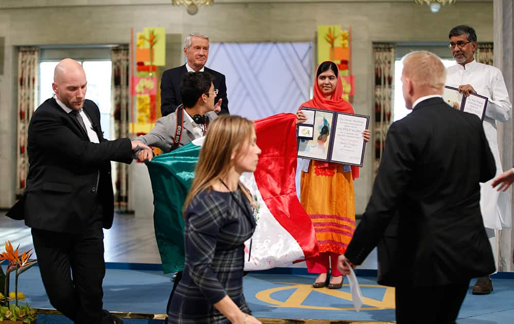 A man holding the Mexican flag is led away by security after attempting to get on stage with Nobel Peace Prize winners Malala Yousafzai from Pakistan and Kailash Satyarthi of India during the Nobel Peace Prize award ceremony in Oslo, Norway.