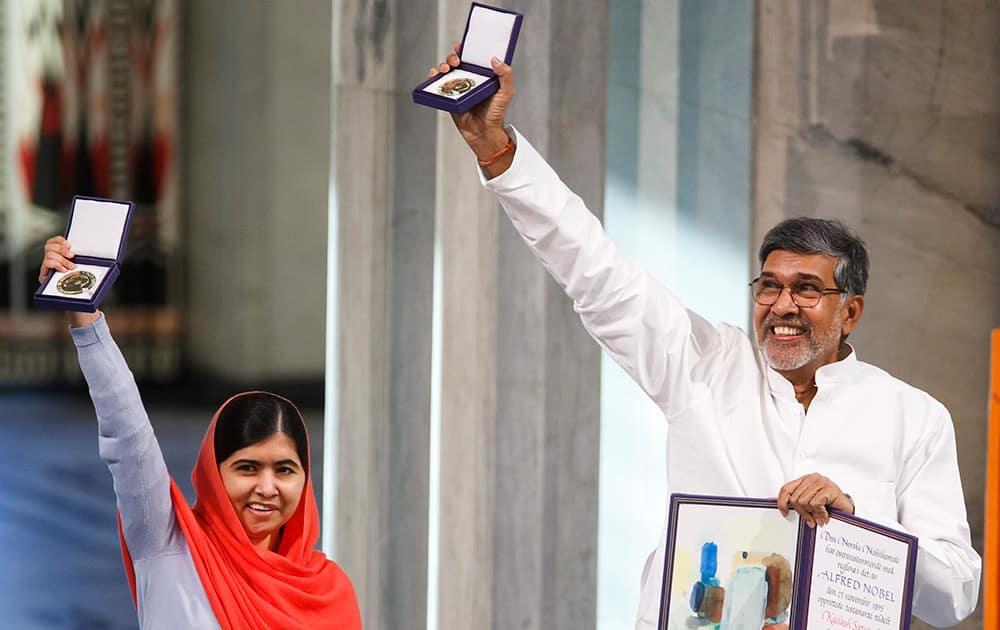 Nobel Peace Prize winners Malala Yousafzai from Pakistan and Kailash Satyarthi of India hold up their Nobel Peace Prize medals during the Nobel Peace Prize award ceremony in Oslo, Norway.