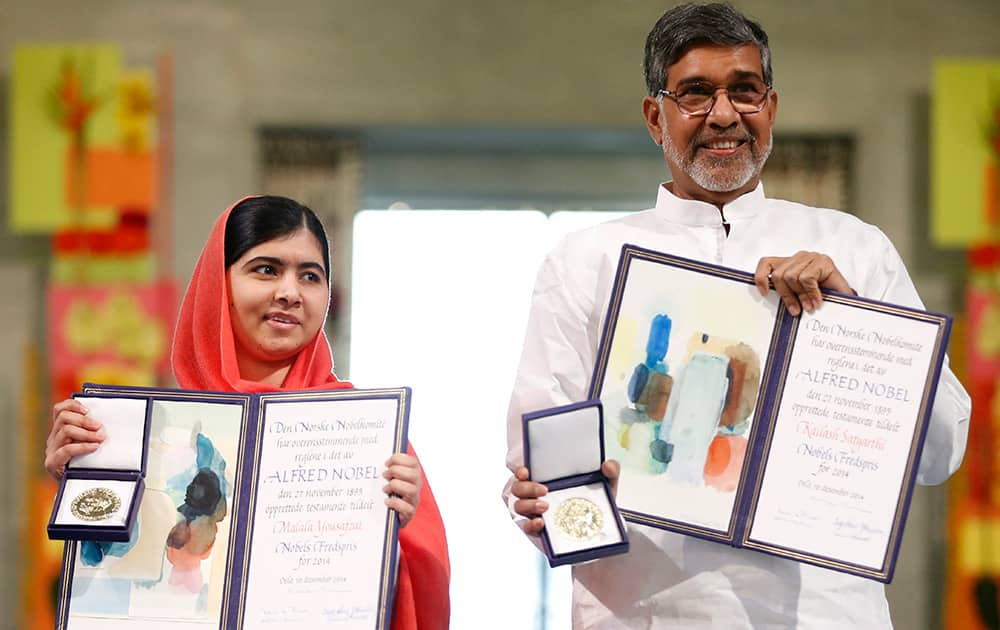 Nobel Peace Prize winners Malala Yousafzai from Pakistan and Kailash Satyarthi of India hold their Nobel Peace Prize diplomas and medals during the Nobel Peace Prize award ceremony in Oslo, Norway