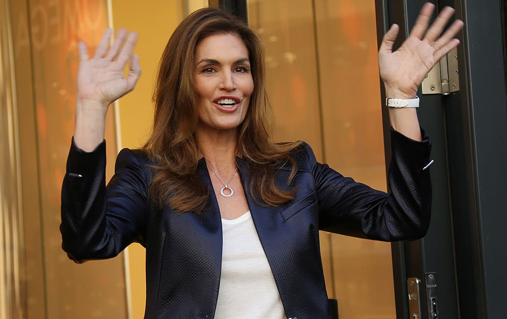Former supermodel Cindy Crawford waves after cutting the ribbon to open the new Omega Boutique on Oxford Street in central London.