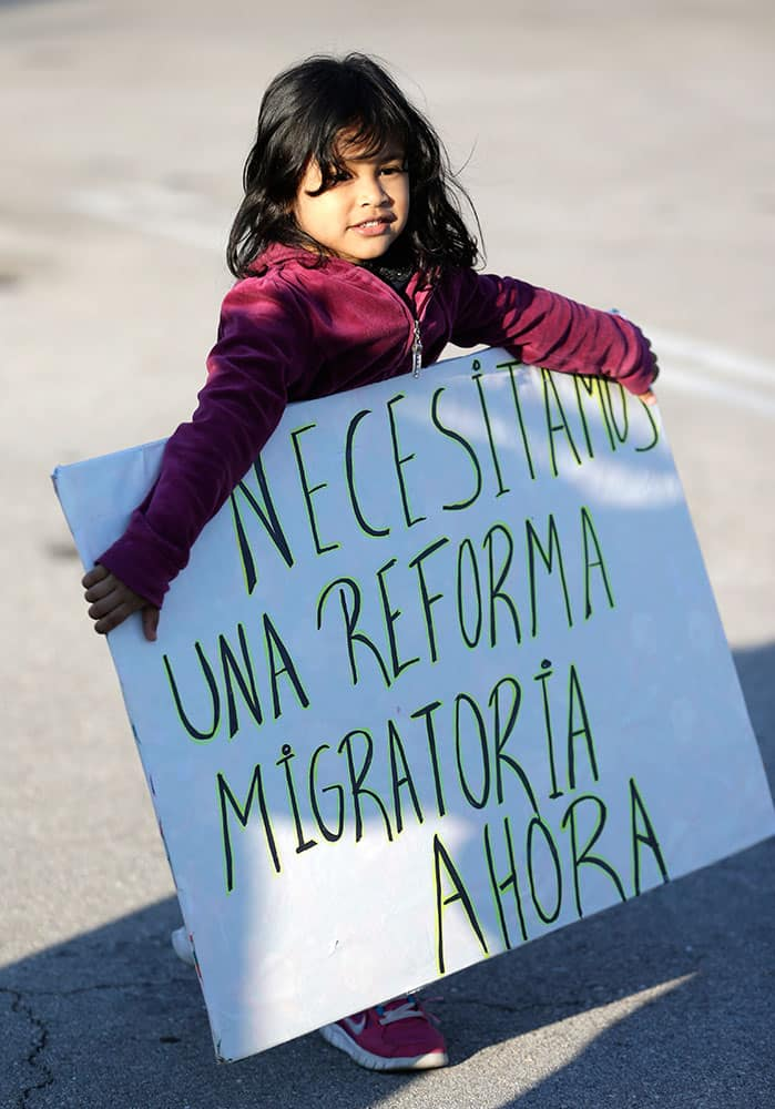 Nayleth Martinez, four-years-old, from Honduras, carries a sign that reads in Spanish