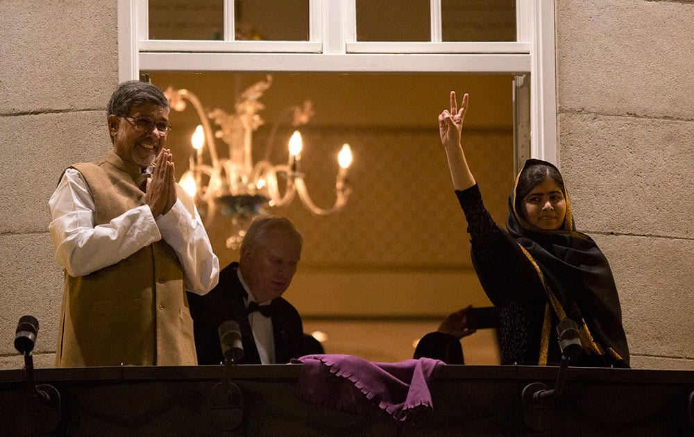 Nobel Peace Prize winners Malala Yousafzai from Pakistan and Kailash Satyarthi of India, left, respond to cheering and applause from a crowd of people as they stand on a balcony of their hotel before attending the Nobel Banquet in Oslo, Norway.