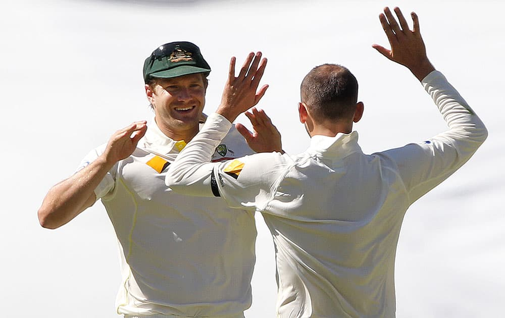 Australia's Shane Watson and Nathan Lyon celebrate after they combined to take the wicket of India's Ajinkya Rahane for 62 runs during the third day of their cricket test match in Adelaide, Australia.