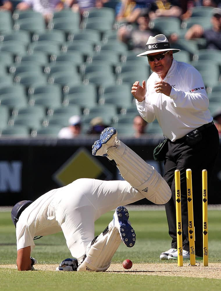 India's Rohit Sharma, dives back to his crease as umpire Marais Erasmus watches during the third day of their cricket test match against Australia in Adelaide, Australia.