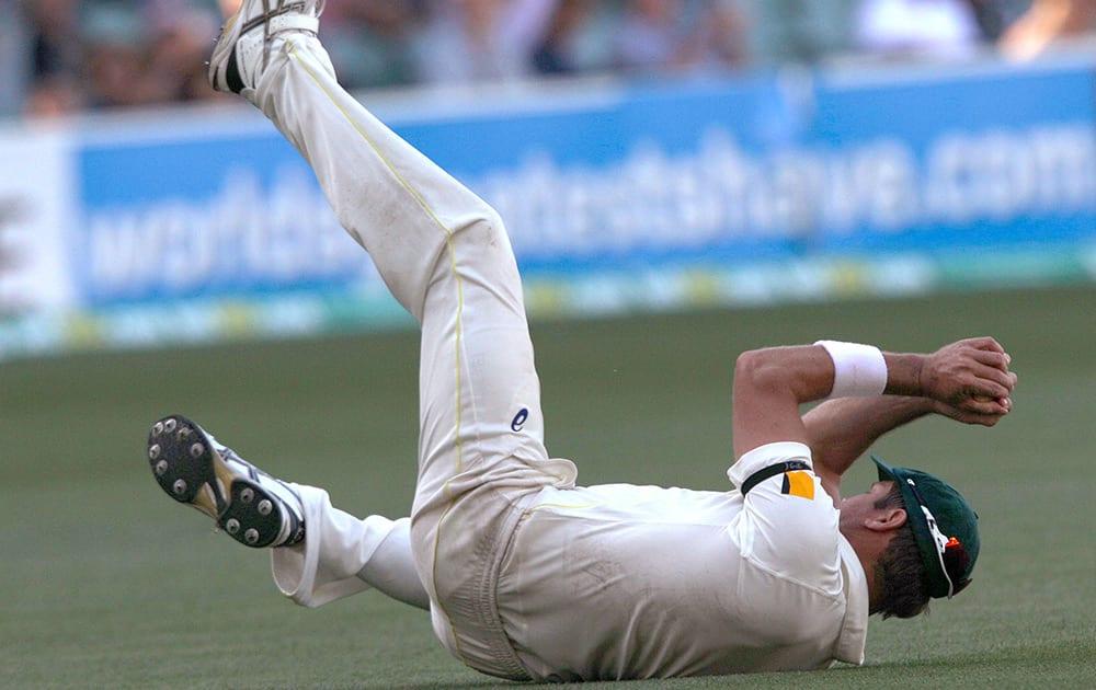 Australia's Ryan Harris catches out India's Virat Kohli for 115 runs during the third day of their cricket test match in Adelaide, Australia.