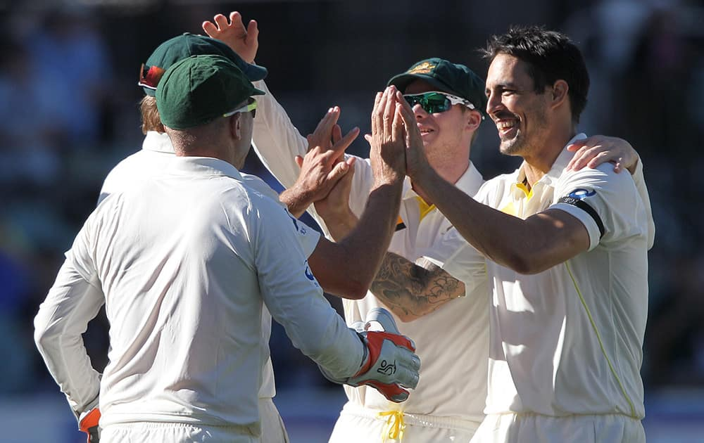 Australia's Mitchell Johnson, celebrates with teammates after taking the wicket of India's Virat Kohli for 115 runs during the third day of their cricket test match in Adelaide, Australia.