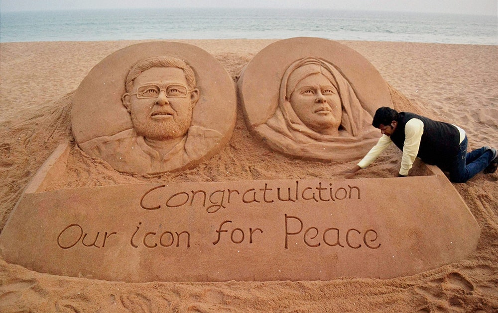 Sand artist Sudarshan Pattnaik gives finshing touches to a sand sculpture of Nobel Peace Prize winners, Kailash Satyarthi and Malala Yousafzai in Puri.