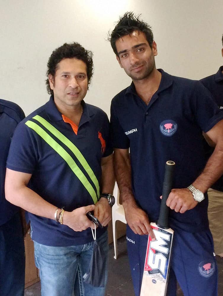 Cricket legend Sachin Tendulkar with a member of the Jammu and Kashmir team that defeated 40-time champion Mumbai in a Ranji Match, in Mumbai.