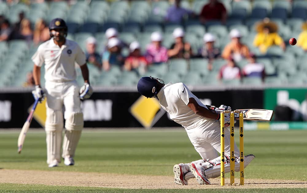 Rohit Sharma, leans back to avoid a high delivery from Australia's Mitchell Johnson as teammate Wriddhiman Saha watches during the third day of their cricket test match in Adelaide, Australia.