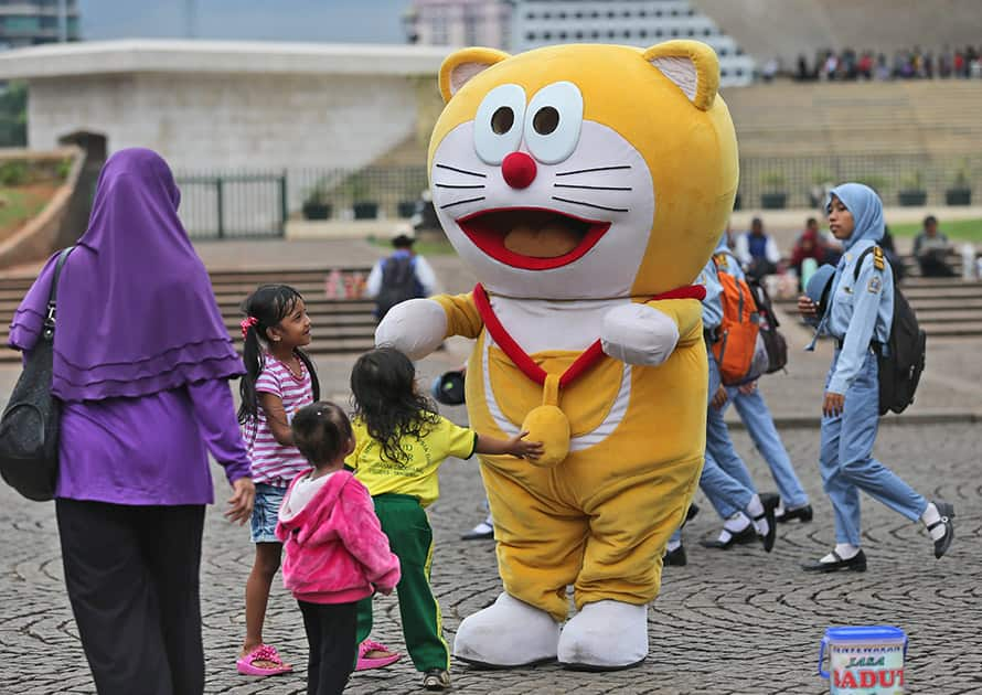 A street busker dressed as Japanese anime character Doraemon plays with children at the National Monumenet in Jakarta.
