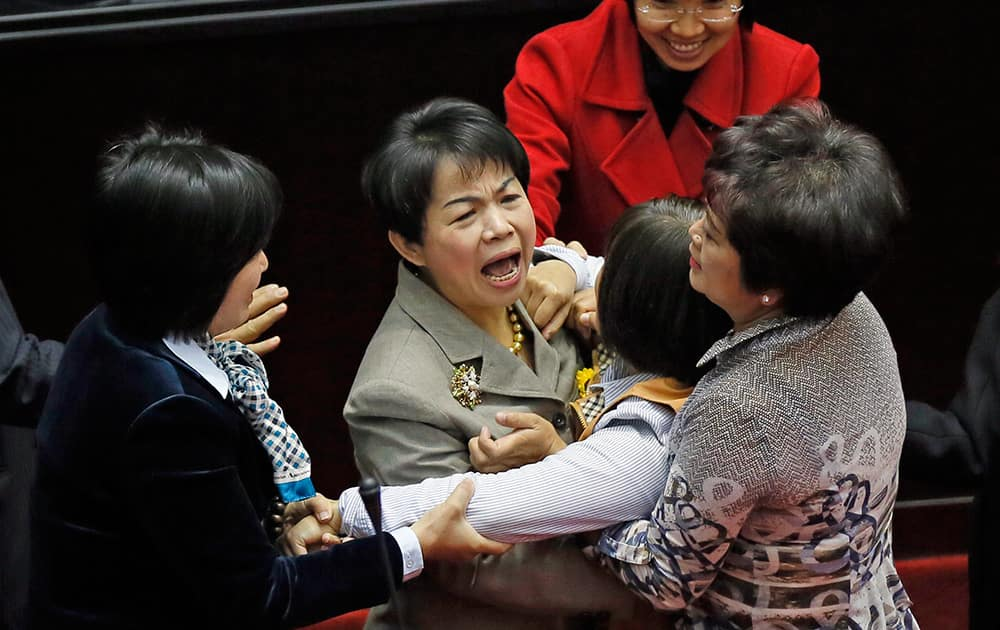 Taiwan's ruling and opposition lawmakers scuffle as they try to block Premier Mao Chi-kuo from speaking on the floor of the legislature in Taipei, Taiwan.