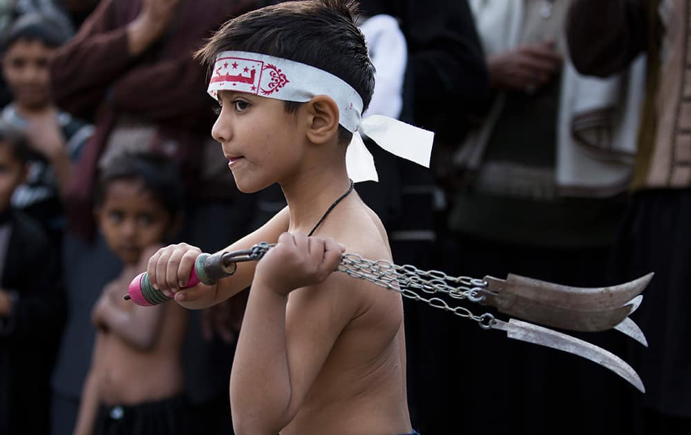 A Pakistani Shiite Muslim boy lashes himself with blades in chains during a Shiite procession observing Chehlum, which traditionally marks a period of mourning for the death of Imam Hussain, grandson of the Prophet Muhammad, in Islamabad, Pakistan.