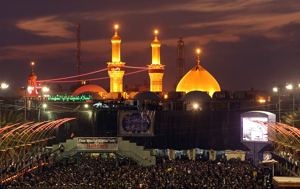 Shiite faithful pilgrims gather between the holy shrine of Imam Hussein and the holy shrine of Imam Abbas, in the background, during the preparations for the Muslim festival of Arbaeen in the Shiite holy city of Karbala, 50 miles (80 kilometers) south of Baghdad, Iraq.