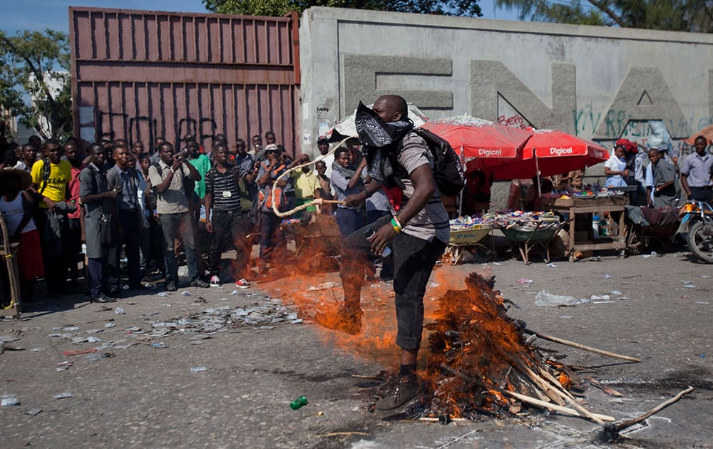 A demonstrator carrying a whip walks over fire in a voodoo ceremony at the start of a protest demanding the resignation of Haiti's President Michel Martelly and Prime Minister Laurent Lamothe in Port-au-Prince, Haiti.