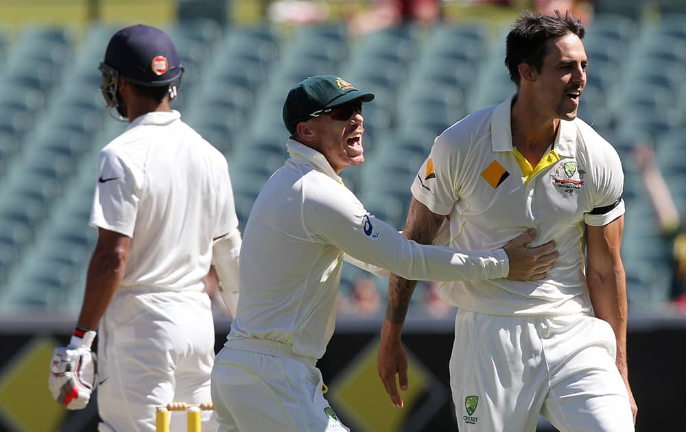 David Warner congratulates teammate Mitchell Johnson, after he dismissed Shikhar Dhawan, during the final day of their cricket test match in Adelaide, Australia