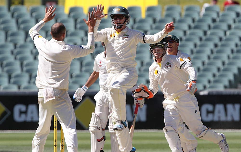 Australia's Chris Rogers leaps in the air to celebrate with teammate Nathan Lyon after catching out India's Ajinkya Rahane for no score during the final day of their cricket test match in Adelaide, Australia.