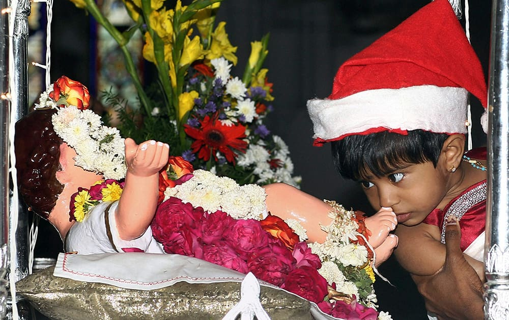 File Photo: A CHILD KISSES THE FEET OF AN INFANT JESUS CHRIST AFTER ATTENDING PRAYER ON THE OCCASION OF CHRISTMAS IN SANTHOME CHURCH IN CHENNAI.
