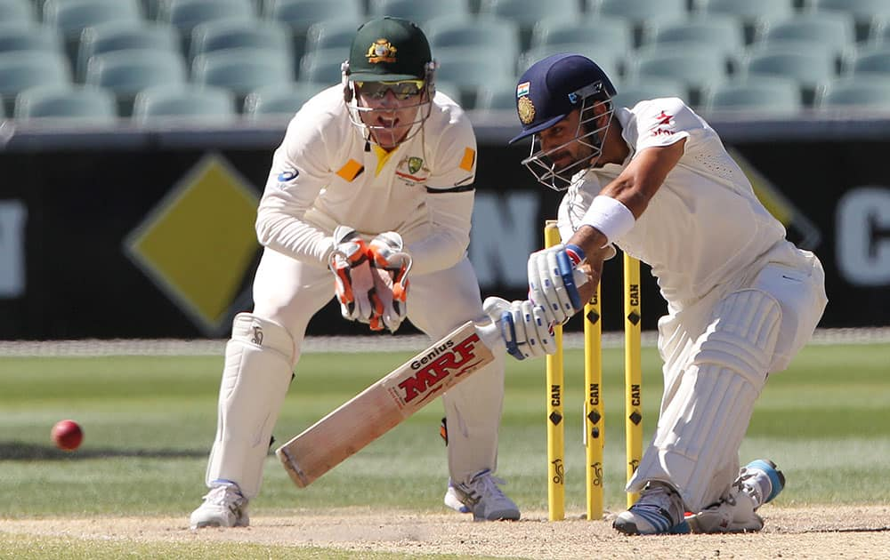 Virat Kohli plays a shot as Australia's Brad Haddin looks on during the final day of their cricket test match in Adelaide.