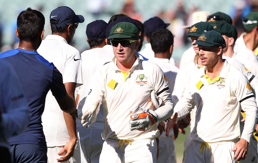 Australia's Brad Haddin and teammate David Warner, shake hands with the Indian players following their 48 run win on the final day of their cricket test match in Adelaide.