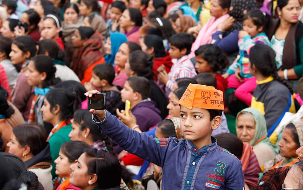 A young boy points his mobile phone towards the stage where Indian Prime Minister Narendra Modi is delivering a speech during an election campaign rally in Kathua, about 90 kilometers from Jammu.