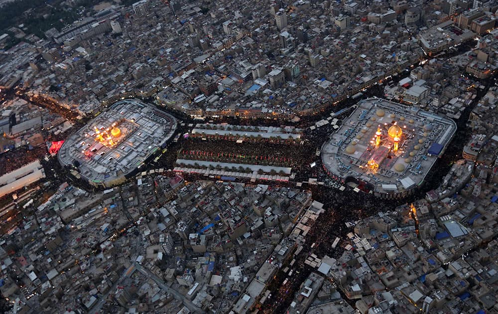 This aerial photo shows Shiite faithful pilgrims gather between, the holy shrine of Imam Hussein and the holy shrine of Imam Abbas, right, for Arbaeen in the Shiite holy city of Karbala, 50 miles (80 kilometers) south of Baghdad, Iraq.
