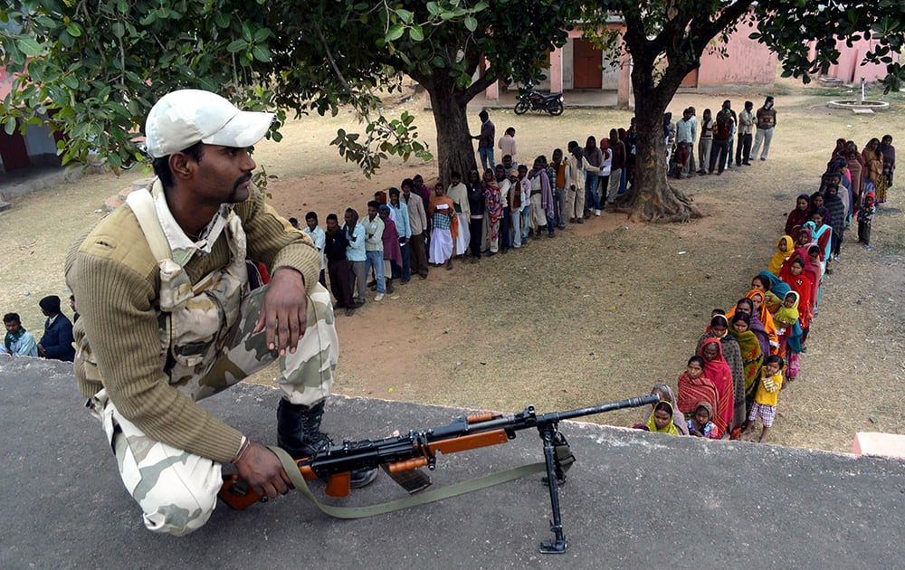 Security person keeps vigil as voters wait in queue to cast their votes in the 4th Phase of Jharkhand Assembly Elections at the naxal hit Tundi consitituency.