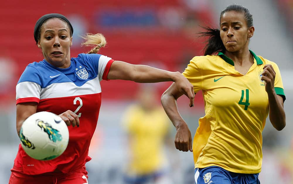 United States' Sydney Leroux, left, fights for the ball with Brazil's Thayla Carolina, right, during a match of the International Women's Football Tournament at the National Stadium in Brasilia, Brazil.