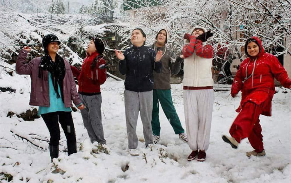 Children enjoying fresh snow after the first snowfall of the season in Kullu.
