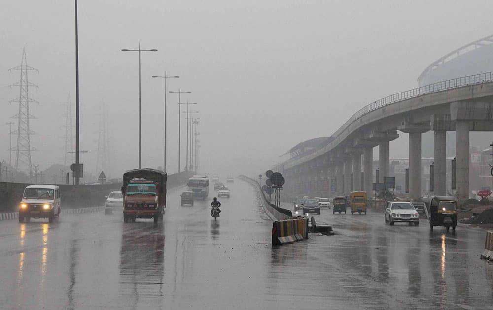 Vehicles run at the Gurgaon- Delhi Expressway during a light drizzling in Gurgaon.