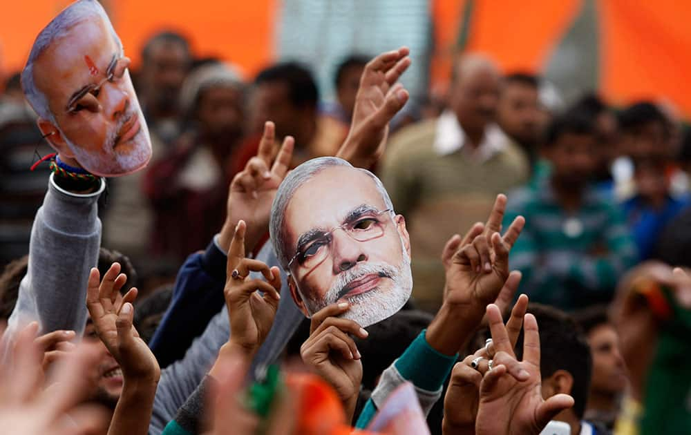 Supporter of India's ruling Bharatiya Janata Party (BJP) hold up masks of Prime Minister Narendra Modi during an election campaign rally in Kathua, about 90 kilometers from Jammu, India, Saturday, Dec.13, 2014.