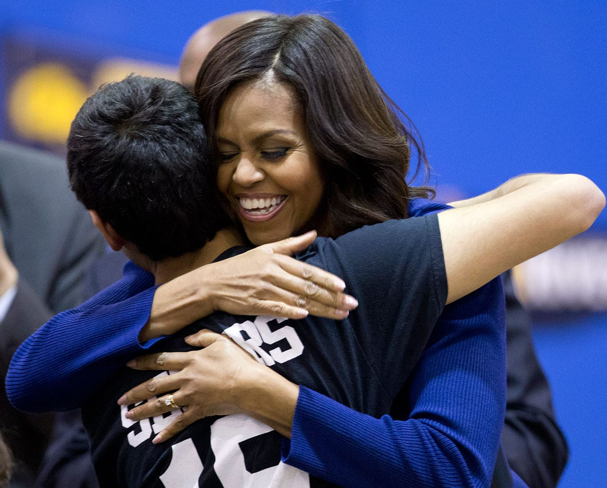 First lady Michelle Obama hugs a Capital City Public Charter School senior after speaking at Capital City Public Charter School in Washington, Friday, Dec. 5, 2014, at the second annual College Application March, part of her Reach Higher initiative.
