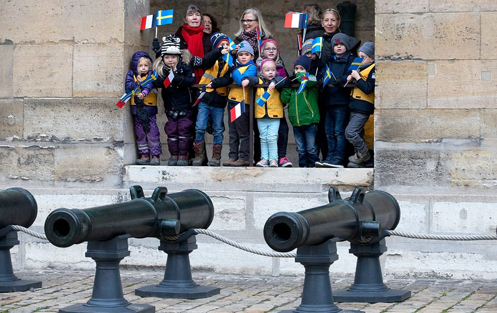School children of the Paris Swedish school attend a military ceremony with Sweden's King Carl XVI Gustaf and Queen Silvia at the Invalides in Paris, Tuesday, Dec. 2 ,2014.