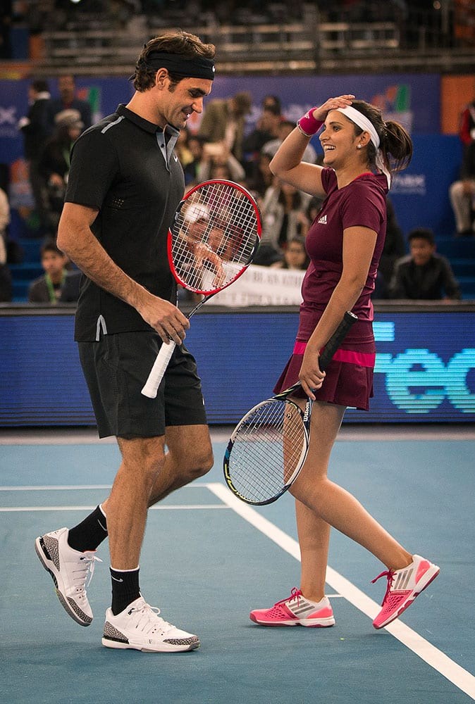 Micromax Indian Aces players Roger Federer, left, talks to Sania Mirza after scoring a point against DBS Singapore Slammers's Bruno Soares and Daniela Hantuchova in the mixed doubles match, during the International Premier Tennis League, in New Delhi, India, Sunday, Dec. 7, 2014.