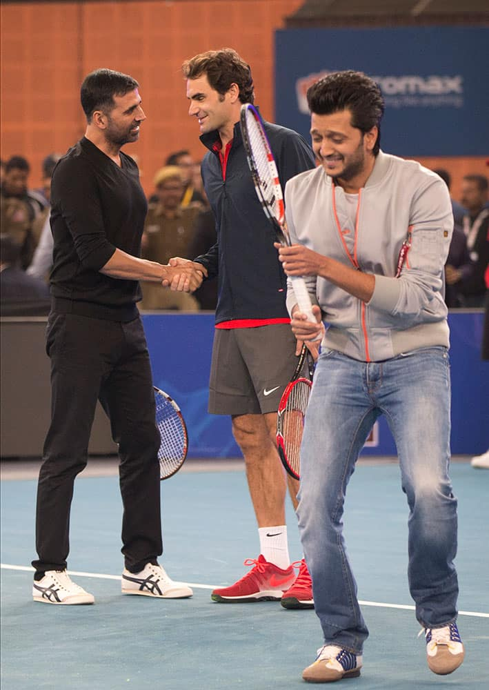Micromax Indian Aces player Roger Federer, shakes hands with Indian Bollywood actor Akshay Kumar, left, as actor Ritesh Deshmukh passes by during a match on the sidelines of the International Premier Tennis League, in New Delhi, India.