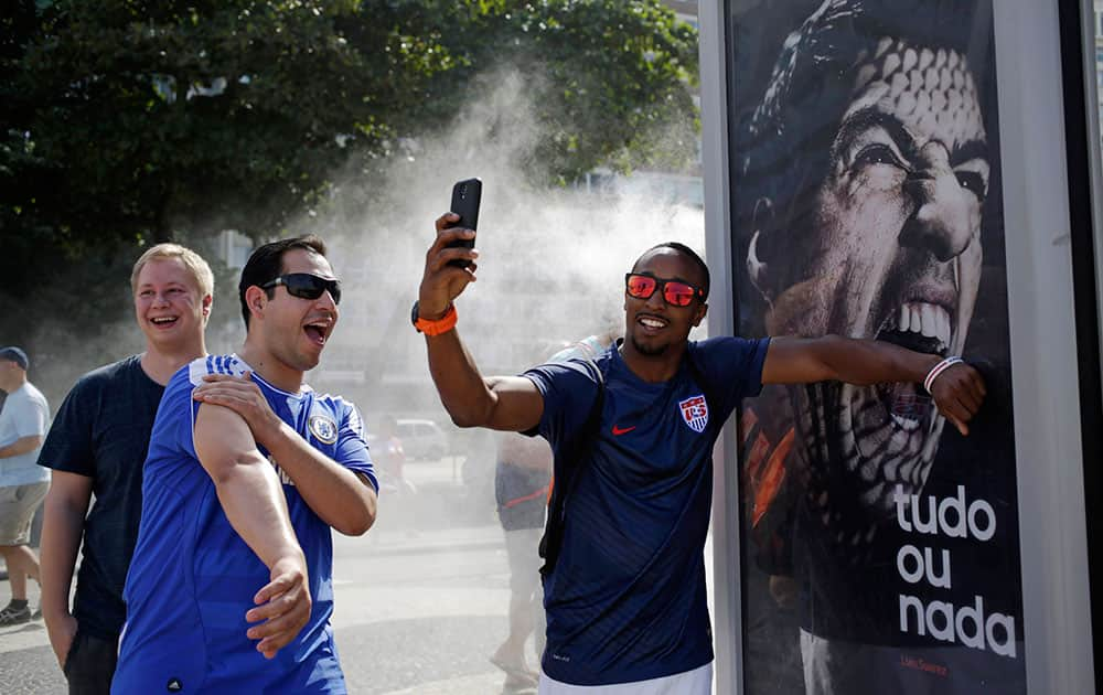 In this June 26, 2014 file photo, a U.S. soccer fan pretends that Uruguay's soccer striker Luis Suarez is biting him as he takes a selfie next to an Adidas advertisement featuring Suarez near Copacabana beach in Rio de Janeiro, Brazil.