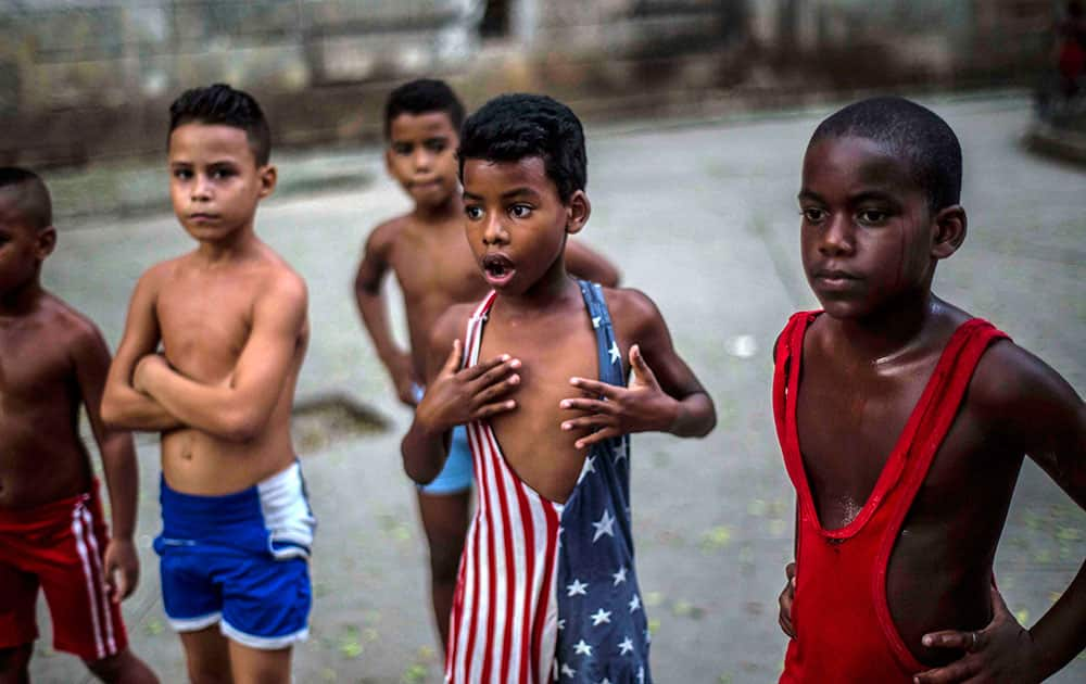 In his Oct. 15, 2014 file photo, 8-year-old Yodimiler Arias, along with fellow wrestlers, listen to instruction from their teacher, in a park in Old Havana, Cuba. Yodimiler's mother said the U.S. flag motif wrestling suit was sent by her cousin in the United States.