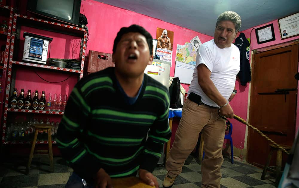 In this June 7, 2014 file photo, 17-year-old Miguel Chusqui grimaces in pain as he is lashed by a