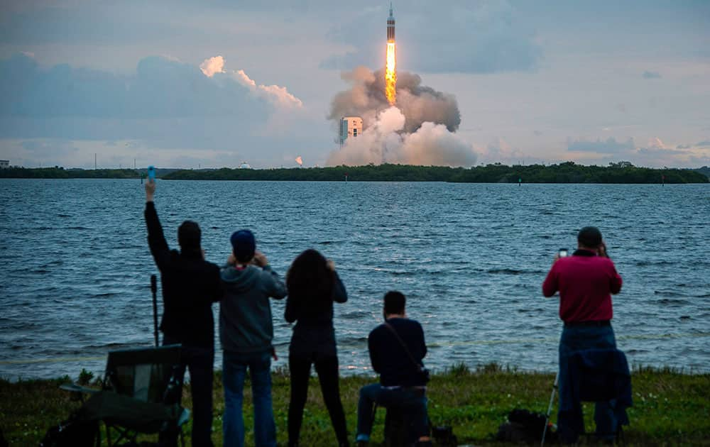 Spectators cheer as the United Launch Alliance Delta 4-Heavy rocket, with NASA's Orion spacecraft mounted atop, lifts off from the Cape Canaveral Air Force Station Friday, Dec. 5, 2014, in Cape Canaveral, Fla.