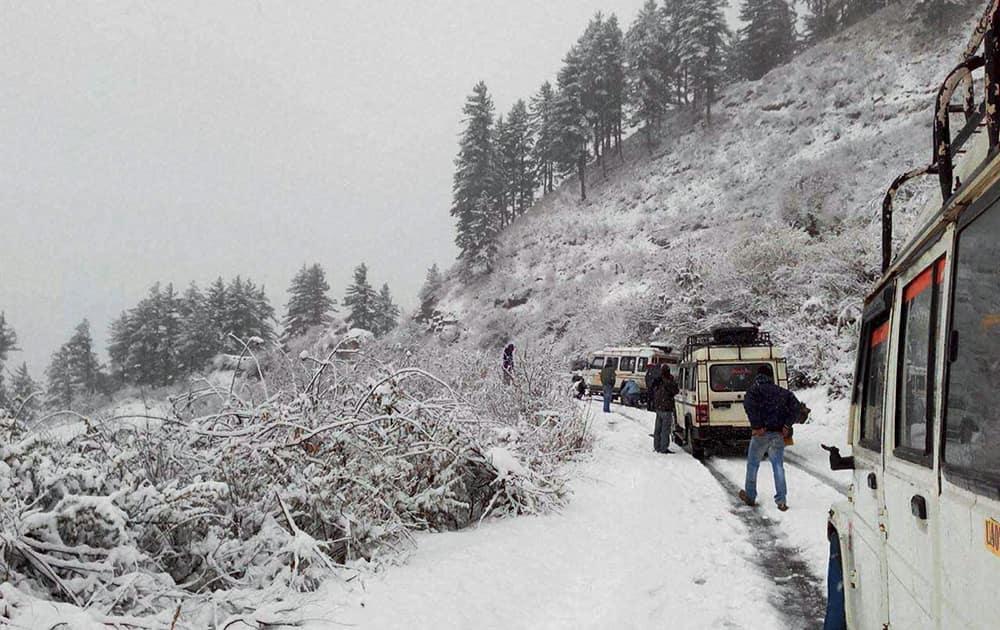 Vehicles move on the snow covered Uttarkashi-Gangotri highway in Uttarakhand.